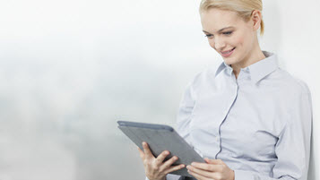 Blonde Frau im Hemd hält Tablet in Händen
