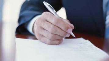 Mann im Anzug füllt mit Kugelschreiber ein Formular aus