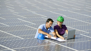 Ingenieur und Ingenieurin aus dem Bereich grüne Technologie mit Laptop in einem Solarfeld