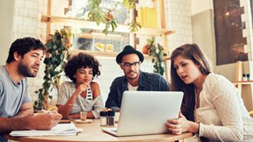 Gruppe junger Menschen sitzen gemeinsam mit Laptop und Dokumenten am Tisch in einem Café
